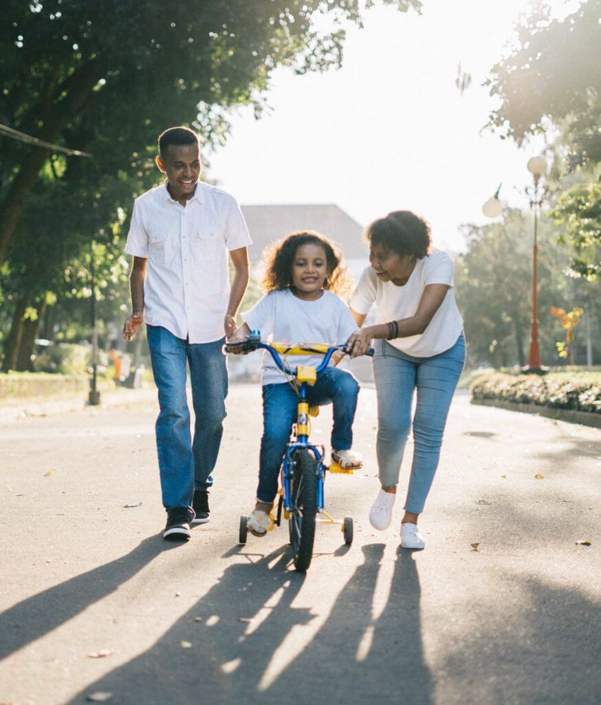 Family playing in the street with young girl riding a bicycle with training wheels