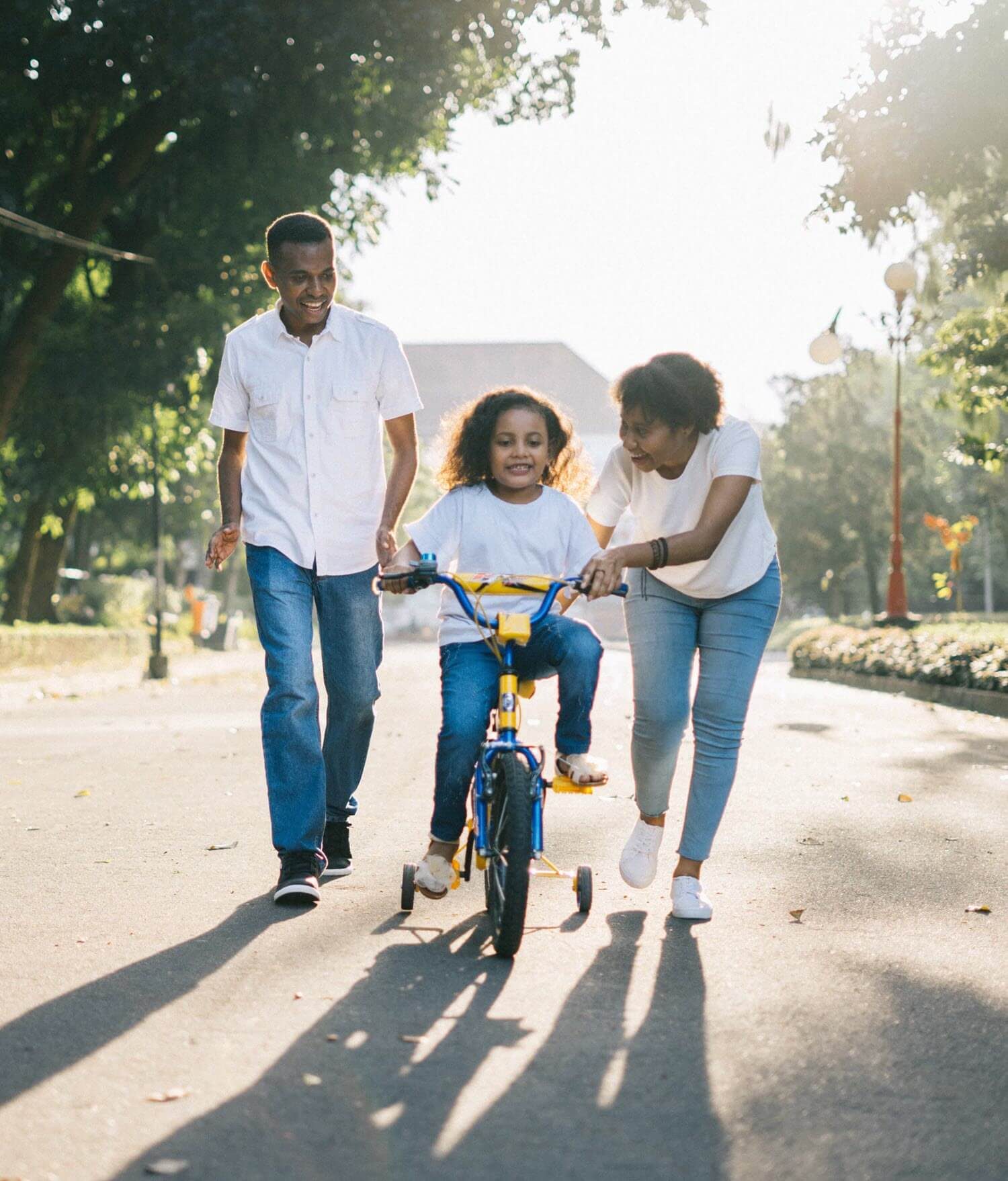African American family playing in the street with young girl riding a bicycle with training wheels